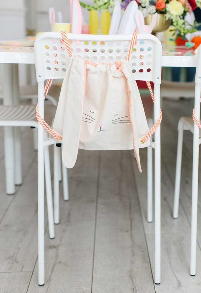 Já pensou em um lugar para colocar as lembrancinhas de Páscoa? Que tal fazer um sacola grande com a carinha do coelho e pendurar na cadeira?