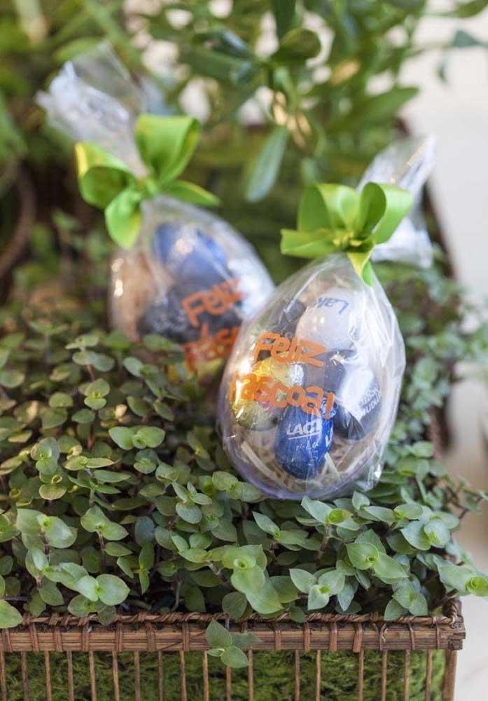 Coloque vários bombons de chocolate dentro de uma embalagem plástica no formato de ovo de Páscoa.
