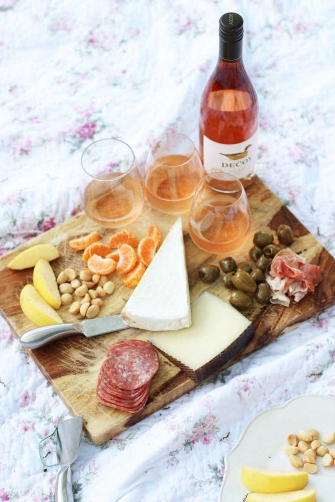 Tábua com queijos, embutidos, azeitonas, frutas e vinhos; opção perfeita para aquela reunião com os amigos