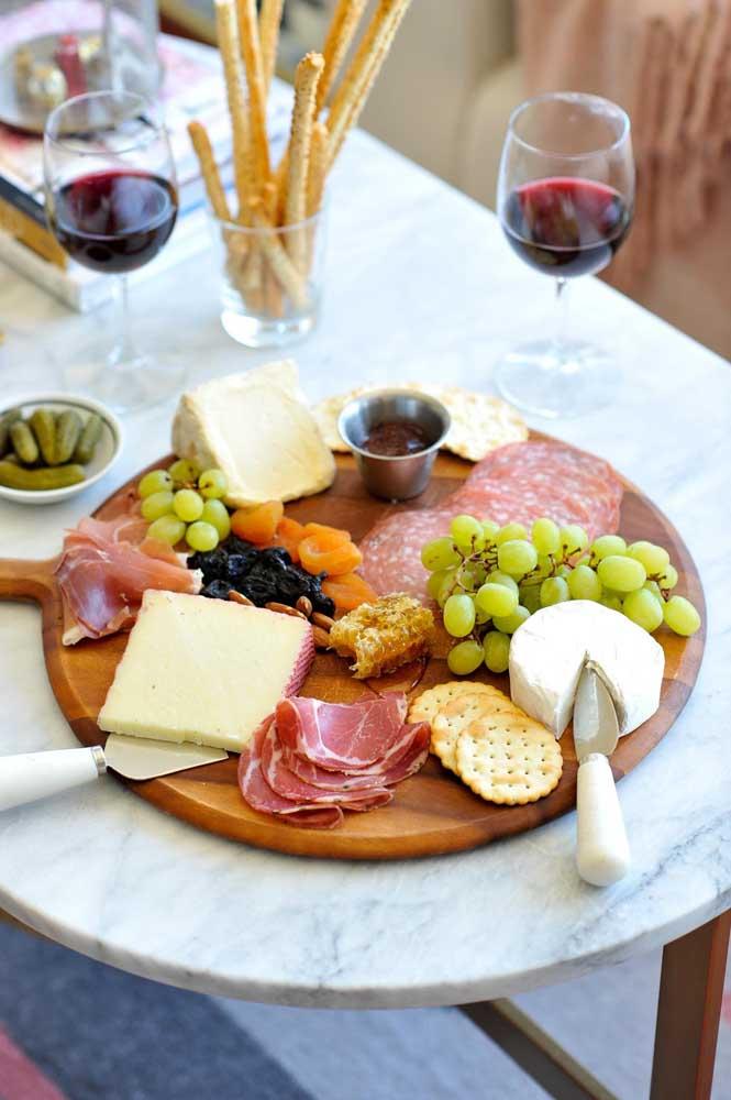 Mesa de frios simples e elegante, com embutidos, bolachas, frutas secas e vinho