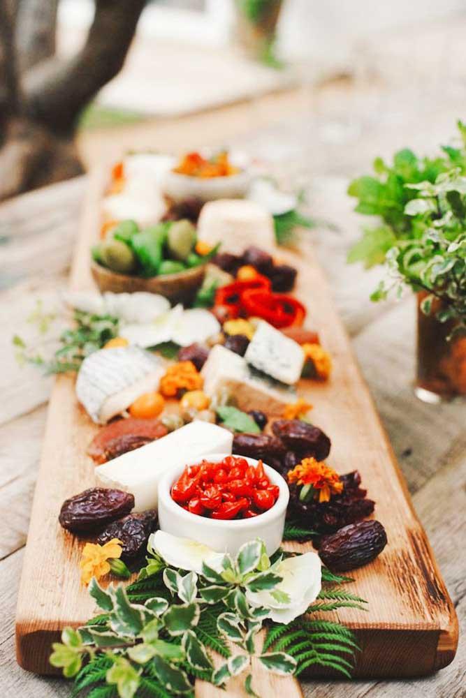 Uma mesa com tábua de frios simples e saborosa, com queijos e ameixas secas; destaque para a decoração com galhos de folhas verdes