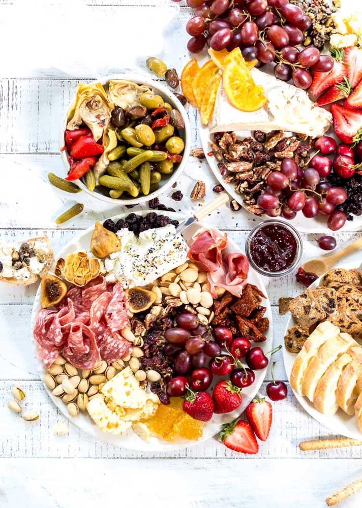 Mesa de frios robusta e cheia de opções, entre elas, embutidos, queijos, azeitonas, uvas e castanhas