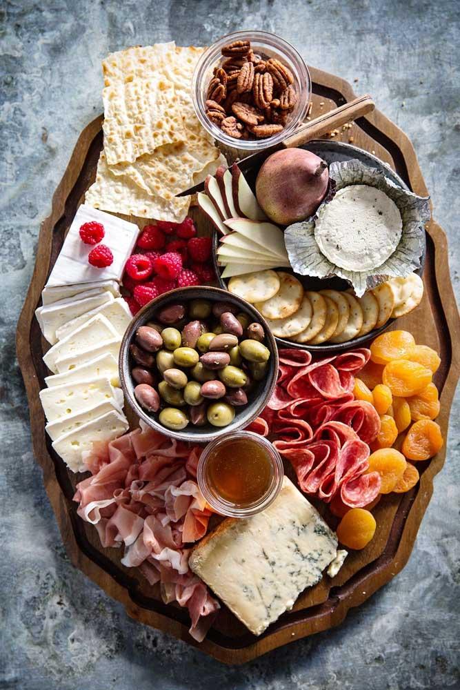 Mesa com tábua de frios recheada de queijos, bolachas, torradas e azeitonas