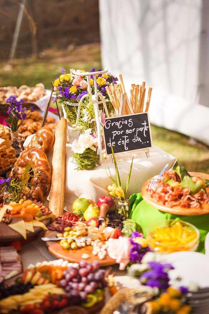 Mesa de frios com pães, torradas, queijos, frutas e ervas; uma opção completa de encher os olhos