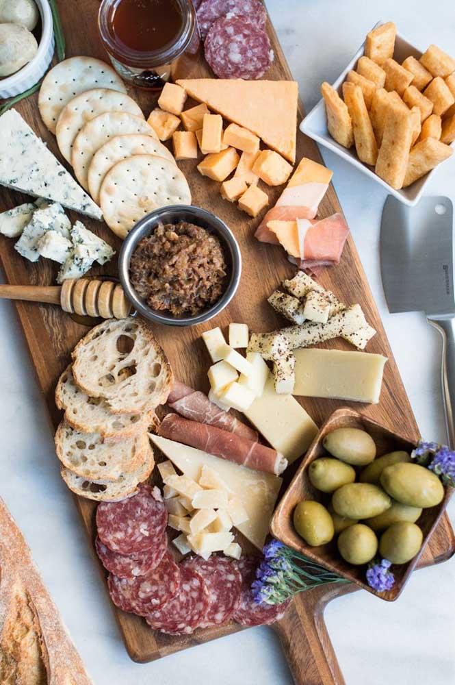 Mesa com tábua de frios simples, com bolachas, queijos e embutidos