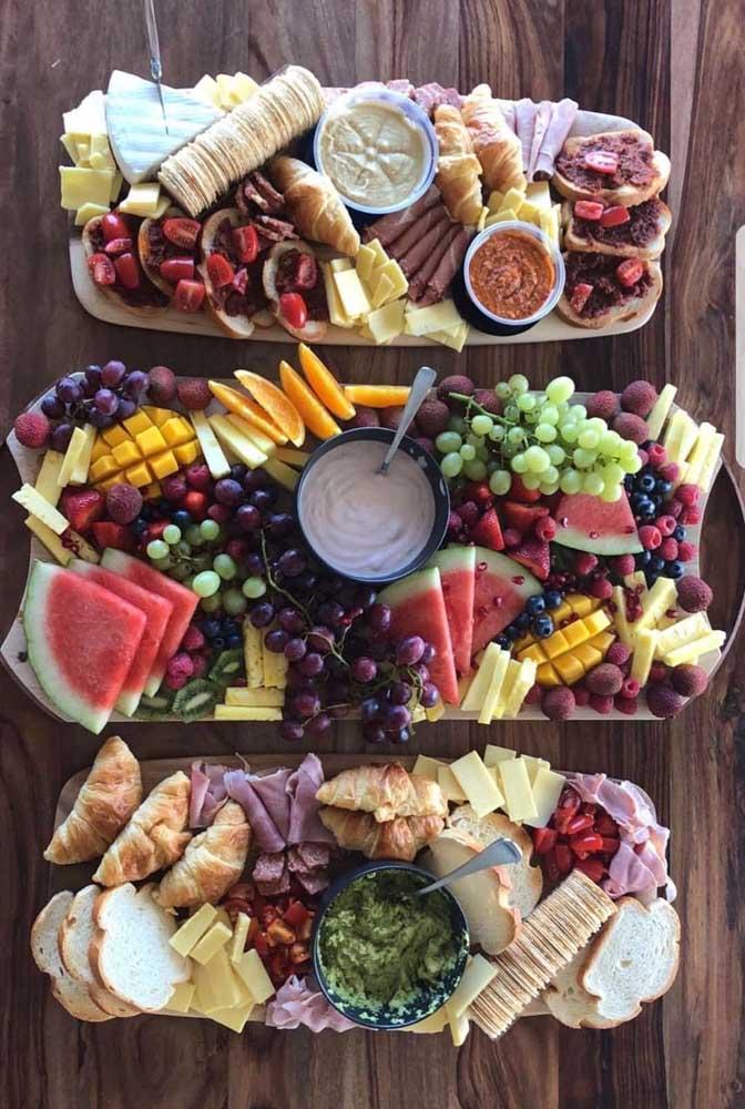 Mesa de frios com pastas, torradas e muitas, muitas, frutas