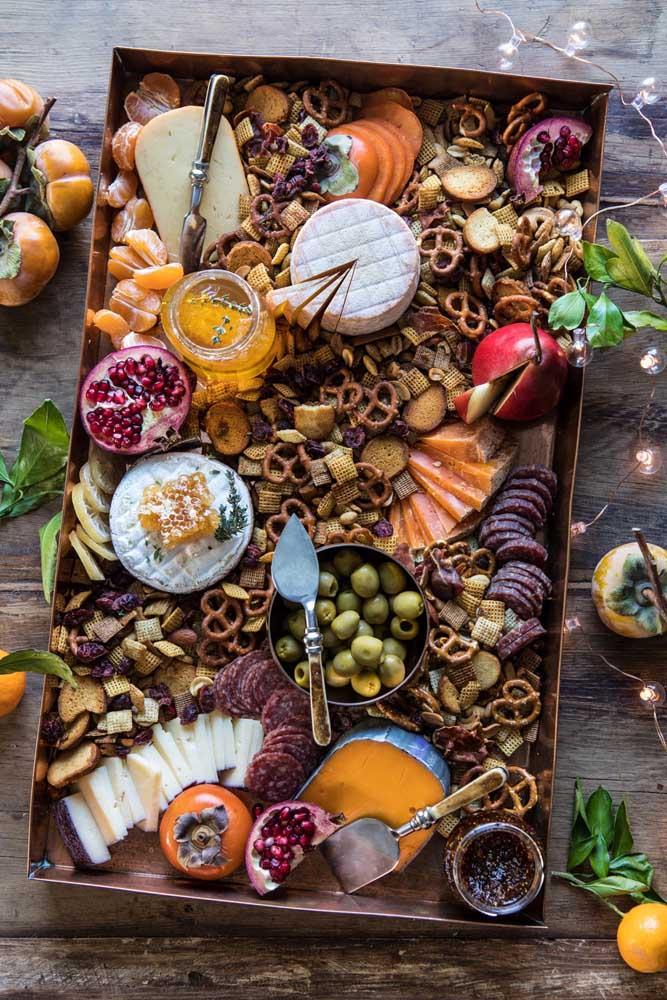 Opção bacana de mesa de frios com pretzels, frutas delicadas e queijos