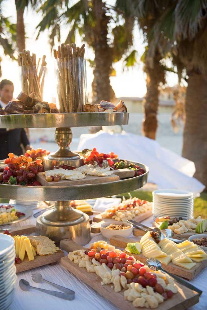 Mesa de frios para casamento com disposição de frutas e queijos organizados por tipos
