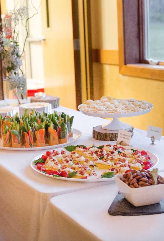 Mesa de frios, com queijos e vegetais servidos em copos