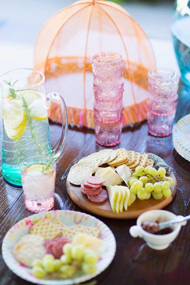 Mesa de frios simples para recepção intimista com queijos e bolachas; para acompanhar, água saborizada