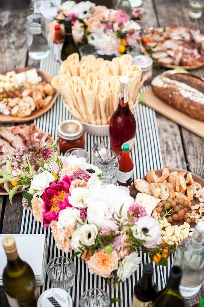 Mesa de frios rústica com queijos e torradas; para decorar, flores