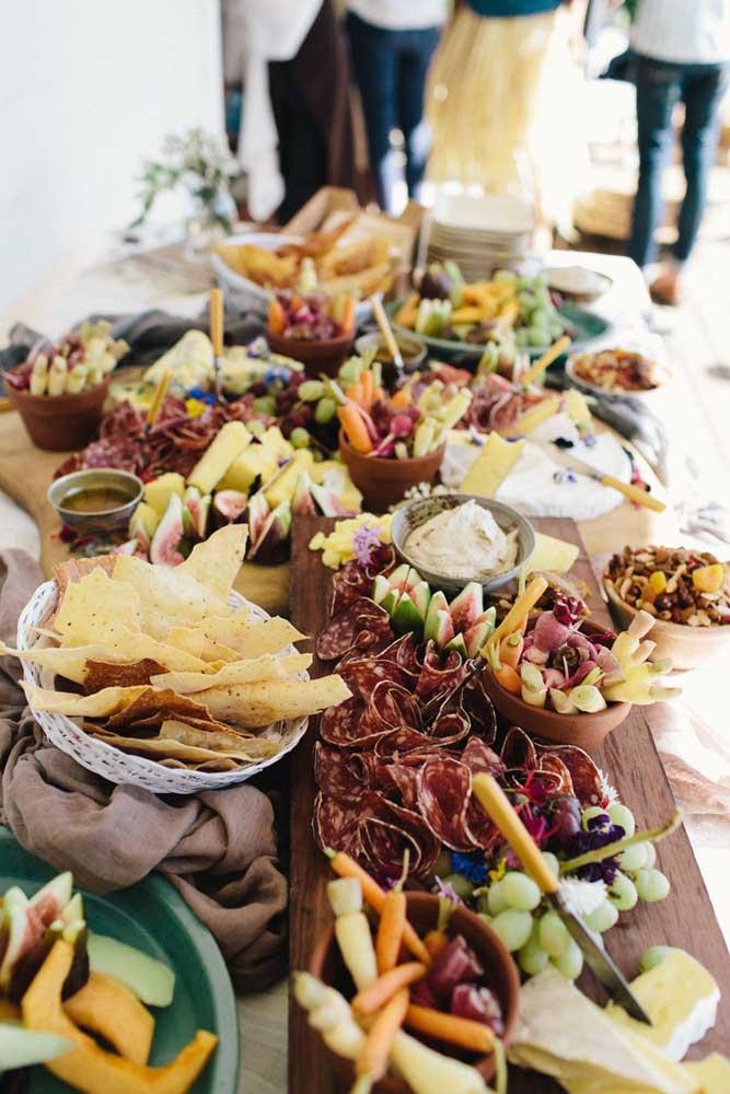 Mesa grande de frios para aniversário com pães, embutidos, vegetais e cremes à disposição