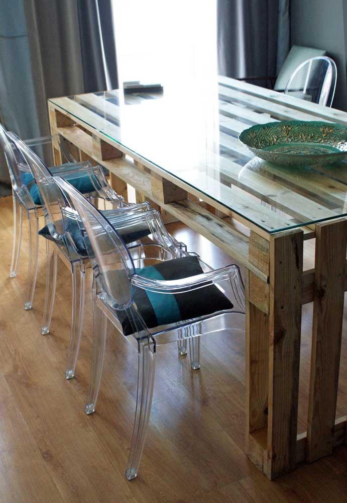 Um toque de elegância e refinamento à mesa de pallets com o tampo de vidro e as cadeiras em acrílico
