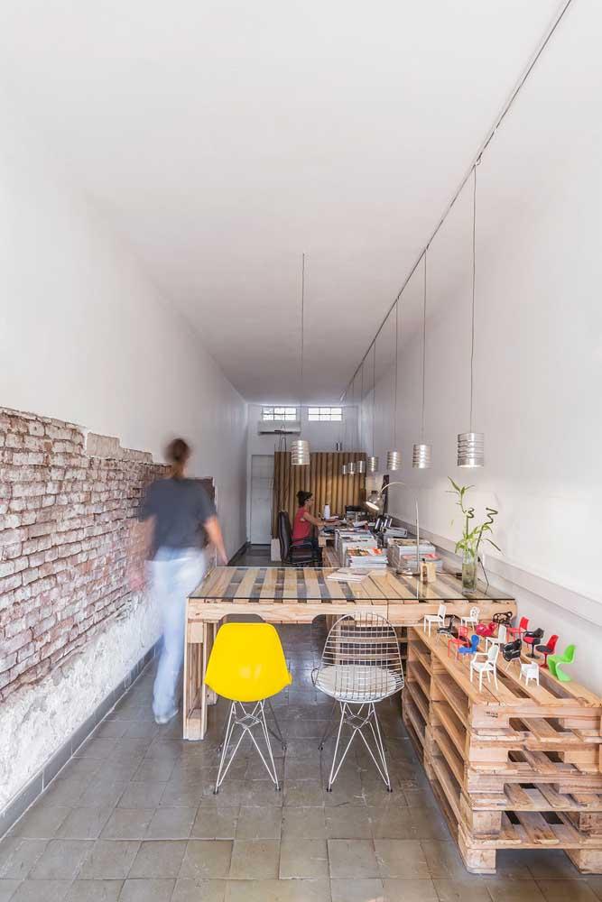 Mais uma sugestão incrível de como usar os pallets para criar mesas de escritório; a parede de tijolinhos completa o visual rústico e despojado do espaço