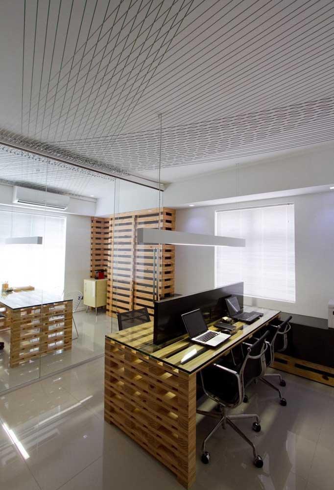 Nesse escritório, as mesas de pallets também ganharam tampos de vidro