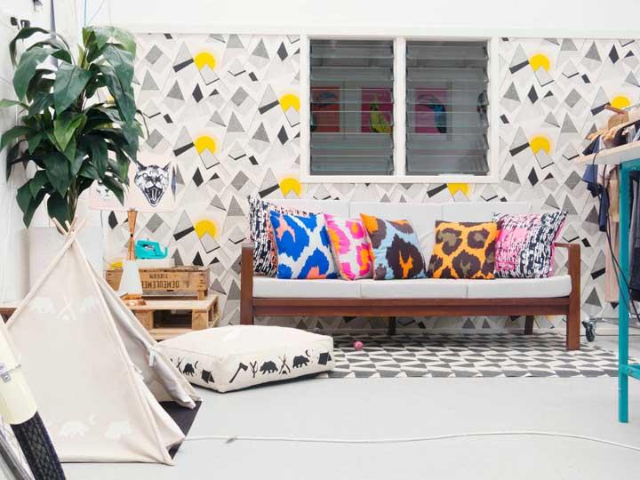 O ambiente moderno e cheio de alegria traz uma mesa de pallets lateral em tom natural