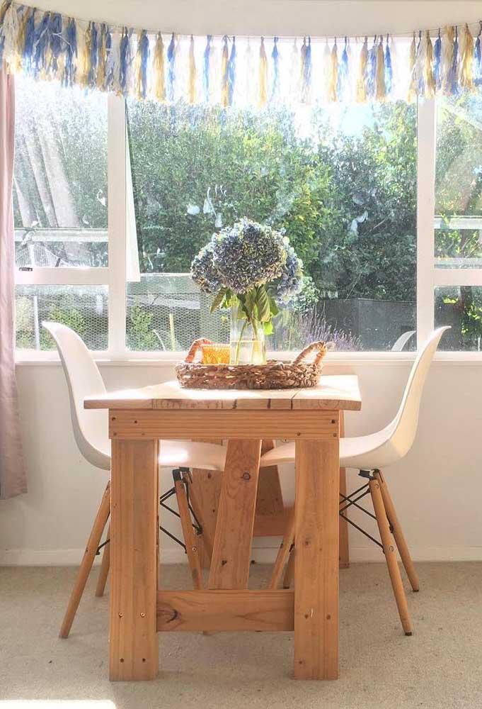 Mesa de pallet pequena para a sala de jantar acompanhada de cadeiras Eames, tendência do momento