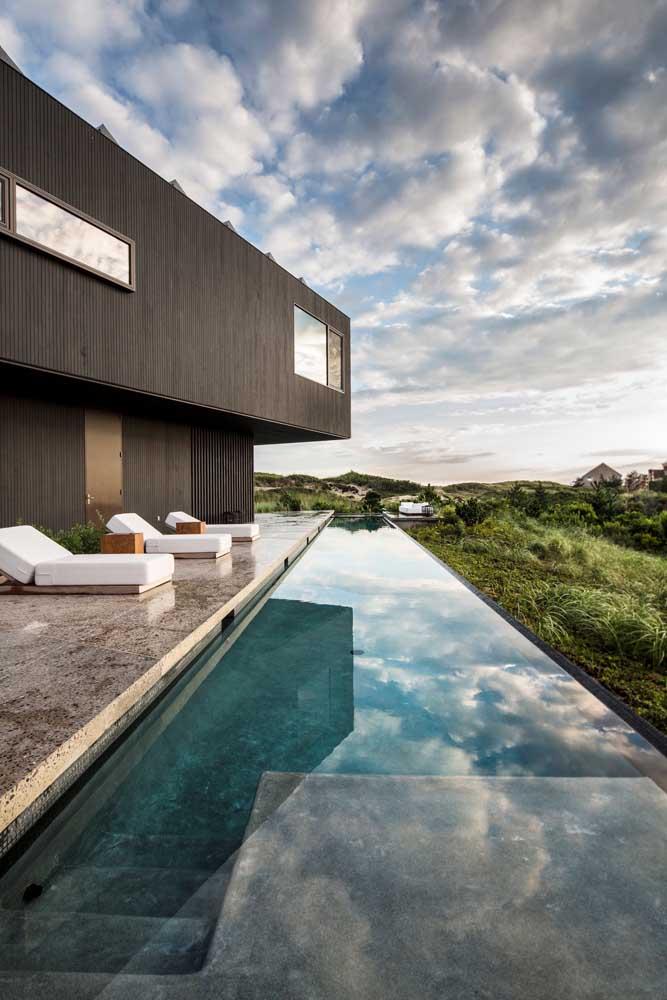 Aqui, o desenho da piscina com borda infinita acompanha o formato da casa