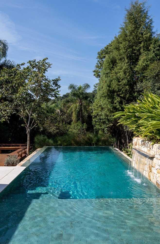 Um modelo de piscina com borda infinita em terreno plano que aproveita a cascata para dar movimento à água que escorre na borda