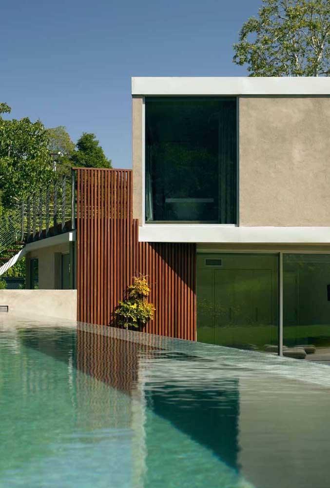 Essa piscina com borda infinita dá a impressão de que a água cai dentro da casa