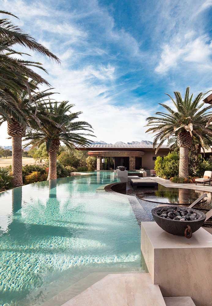 O design tropical da área externa dessa casa combinou super bem com a piscina de borda infinita