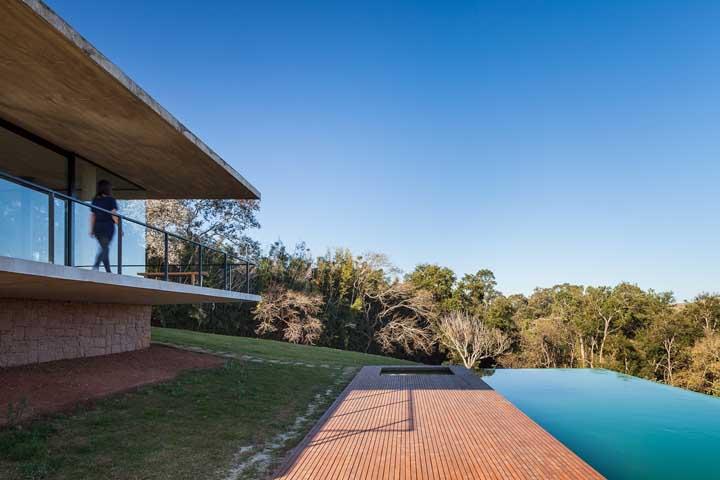 Aqui, o deck de madeira garante o acesso à piscina de borda infinita