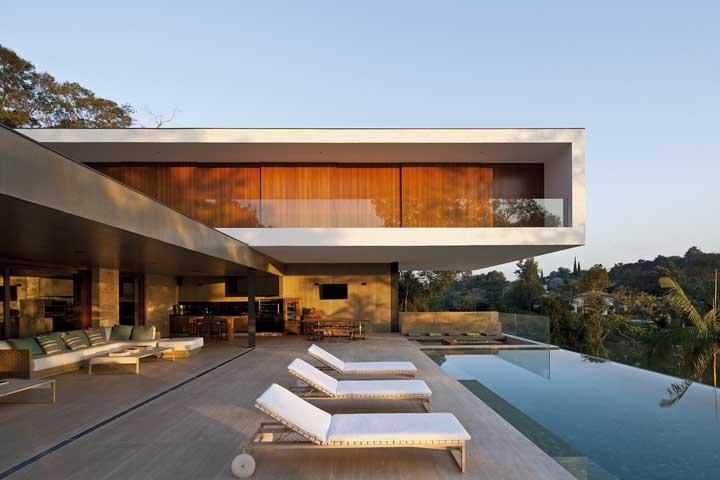 Casa moderna com piscina de borda infinita pronta para receber quem chega