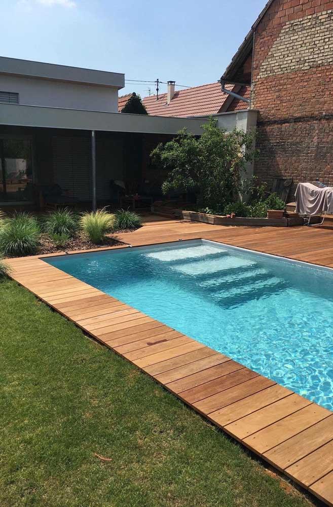 As plantas e o deck de madeira deixam o espaço ao redor da piscina mais convidativo e acolhedor