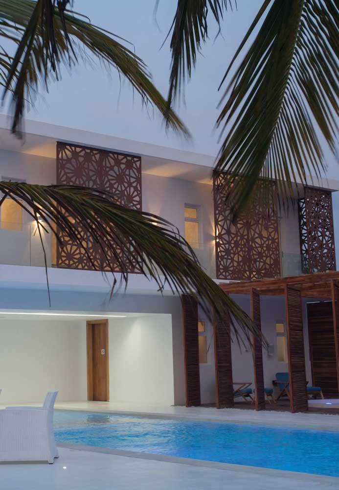 Nesse projeto, a piscina de fibra ocupa parte sob a cobertura da casa e parte ao ar livre