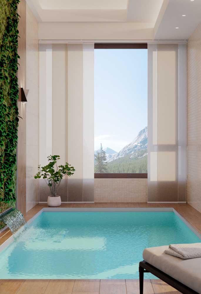 Já esse outro projeto de piscina de fibra em área interna conta com um vistoso jardim vertical junto à cascata de água