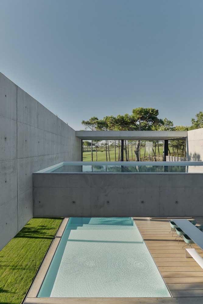 Duas opções de instalação da piscina de fibra no mesmo local: uma no chão e outra sobre o solo com revestimento de concreto aparente