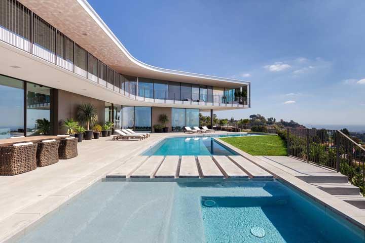 Linda opção de piscina de fibra sob medida acompanhando o design da casa; destaque para a passagem em concreto aparente