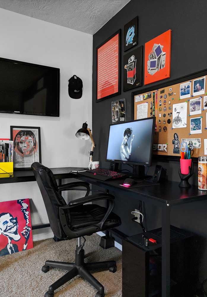 Quarto gamer simples decorado com parede preta e quadros coloridos