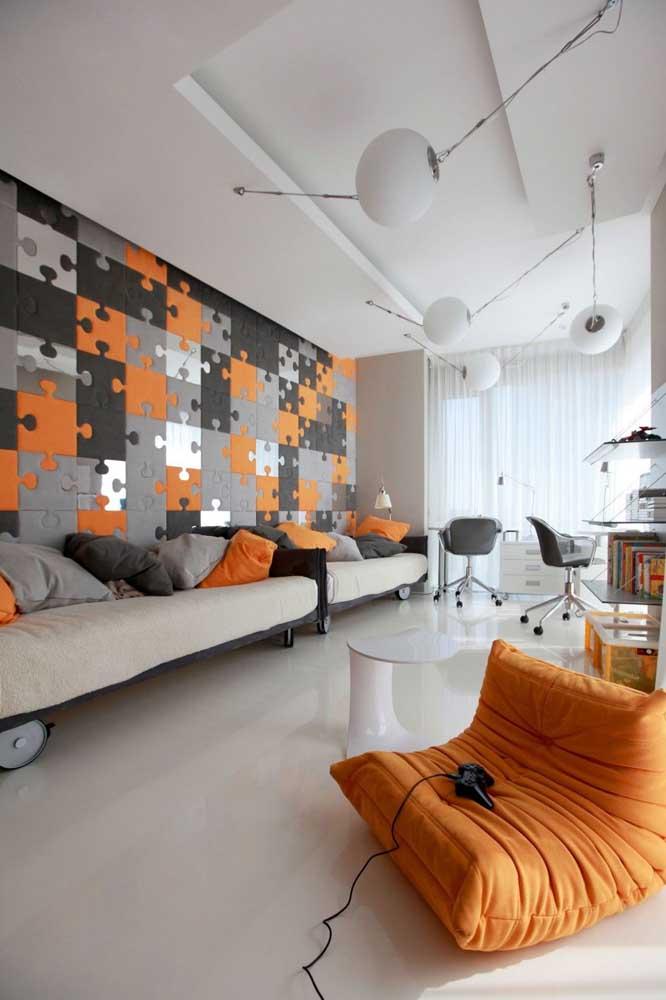 Preto, branco e laranja são as cores que formam a decoração desse quarto gamer amplo e espaçoso