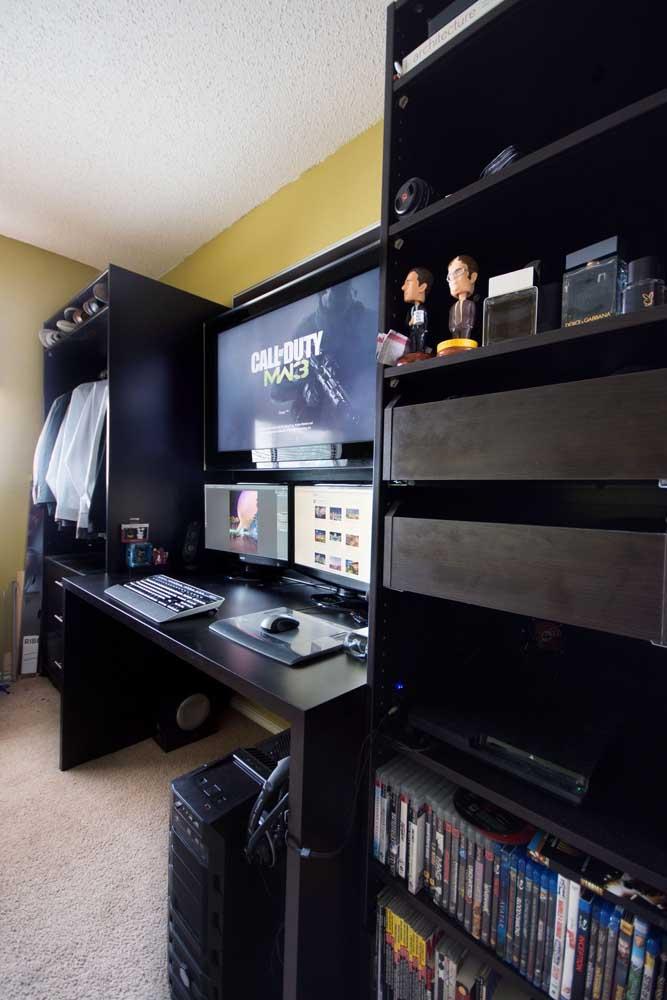 Quarto gamer com destaque para a mesa de jogos com duas telas de PC e uma TV instalada mais acima