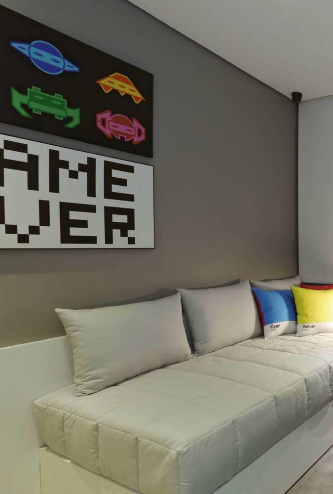 Nesse quarto gamer, a decoração é simples: parede cinza para os quadros e uma cama que pode ser usada como sofá