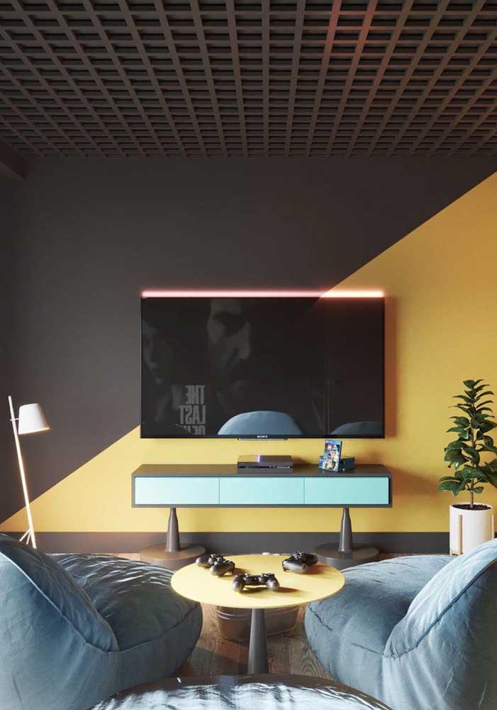 Uma ideia simples e incrível para o quarto gamer: meia parede em preto e amarelo divididas na diagonal