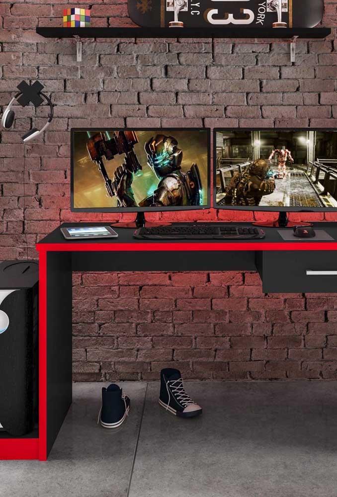 A parede de tijolinhos traz um toque rústico e moderno ao quarto gamer; o uso do preto e do vermelho deixa a proposta ainda mais interessante