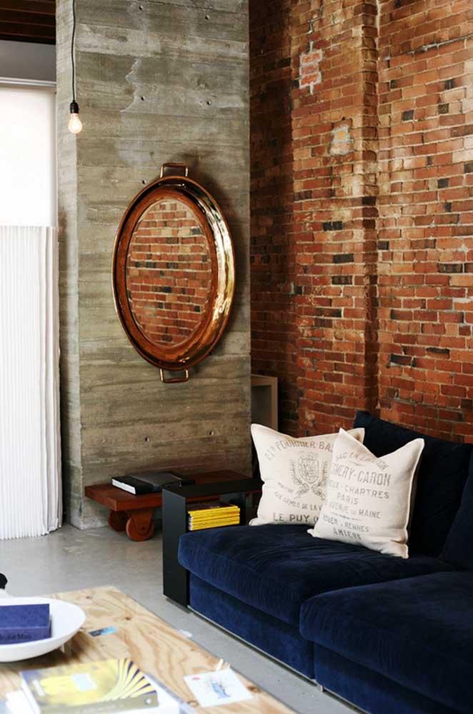 A rusticidade da sala de estar industrial contou com o charme refinado do sofá azul de veludo