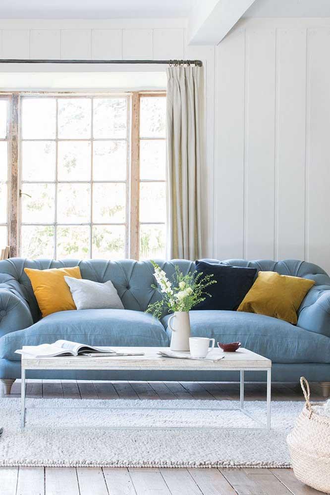 Sofá azul claro com quatro lugares; as almofadas em tom de mostarda trazem cor e vida à decoração