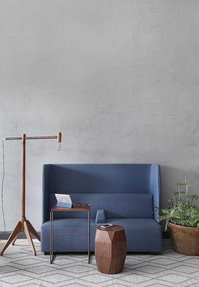 De conceito moderno, esse pequeno sofá azul de linhas retas ficou perfeito na companhia das peças de madeira