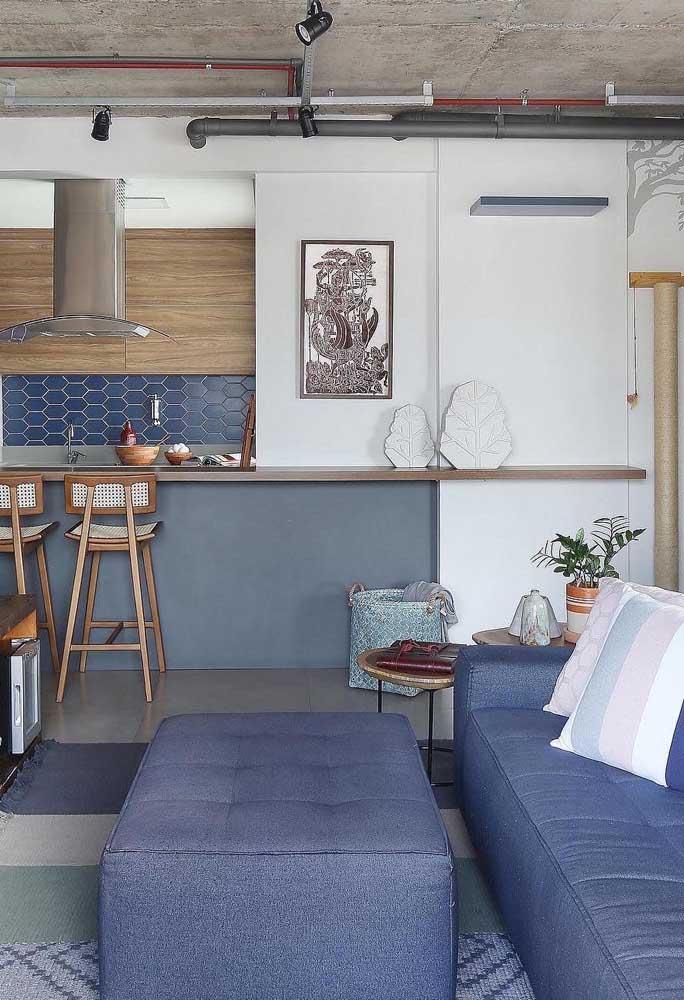 O azul petróleo está por todos os lados nesse ambiente integrado, da cor do sofá ao revestimento da parede da cozinha