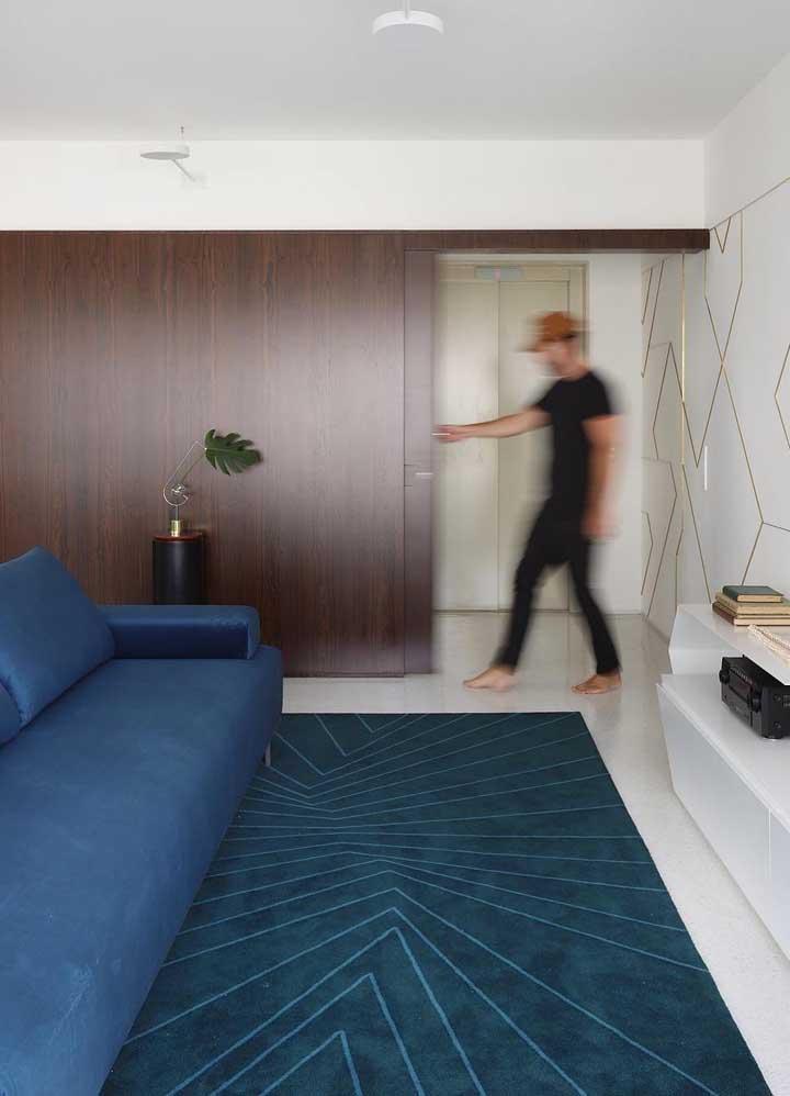 Esse sofá azul petróleo divide a atenção com o tapete em tom parecido; a parede de madeira escura, por sua vez, finaliza a proposta com elegância e refinamento