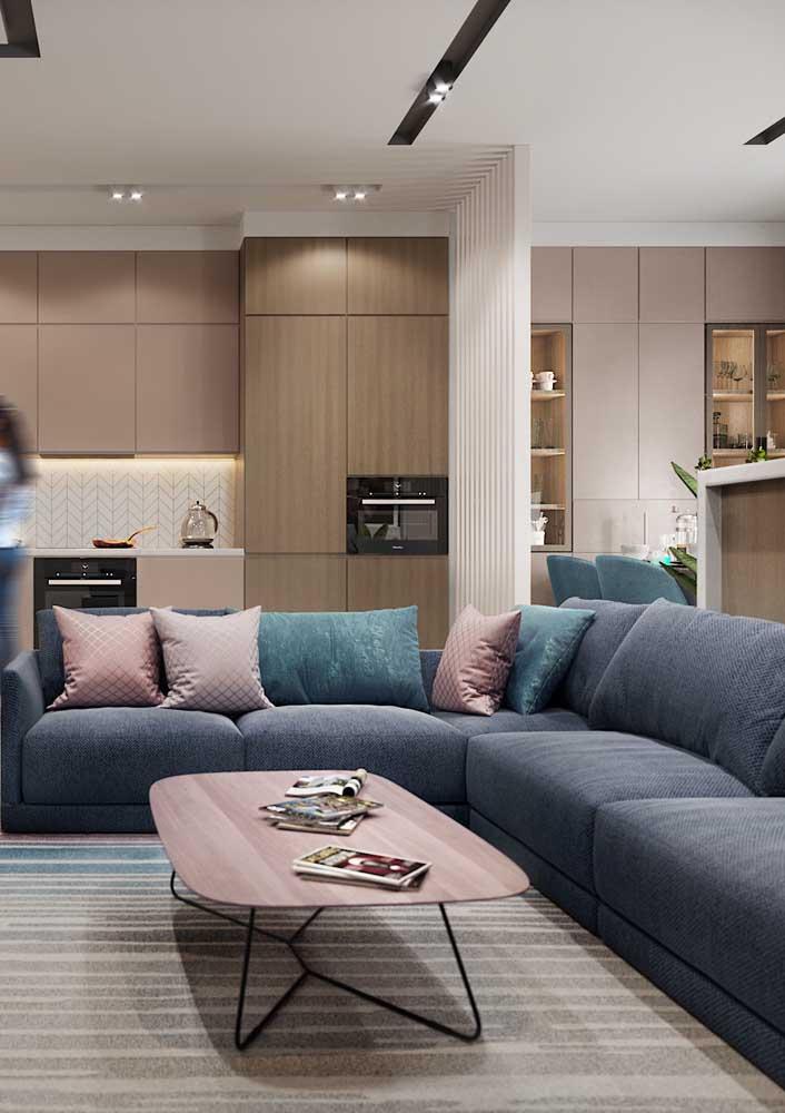 Repare nessa sala de estar como o tom de rosa se harmoniza muito bem com o azul petróleo do sofá