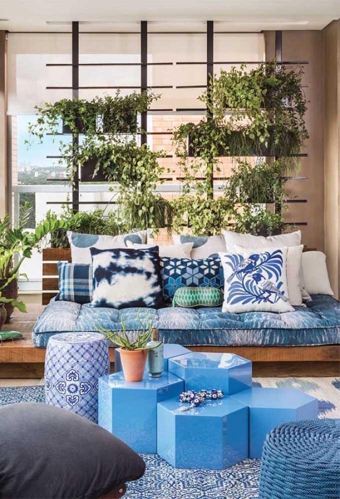 Espaço aconchegante decorado com sofá de base de madeira e futons azuis