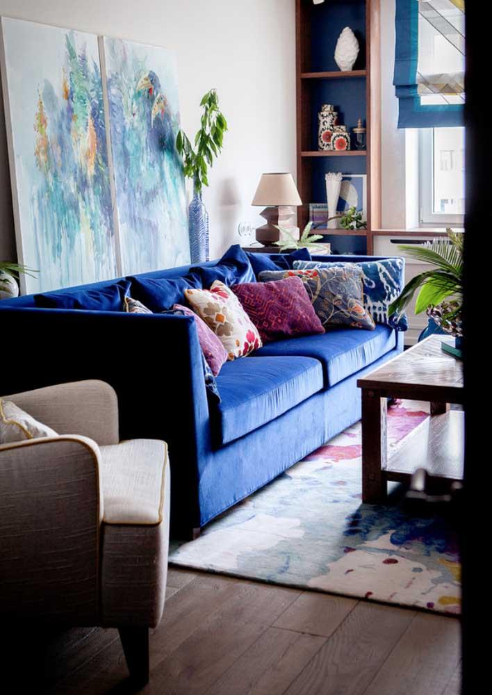 Aqui, o sofá azul royal recebe com muito gosto as almofadas de cores vivas e alegres