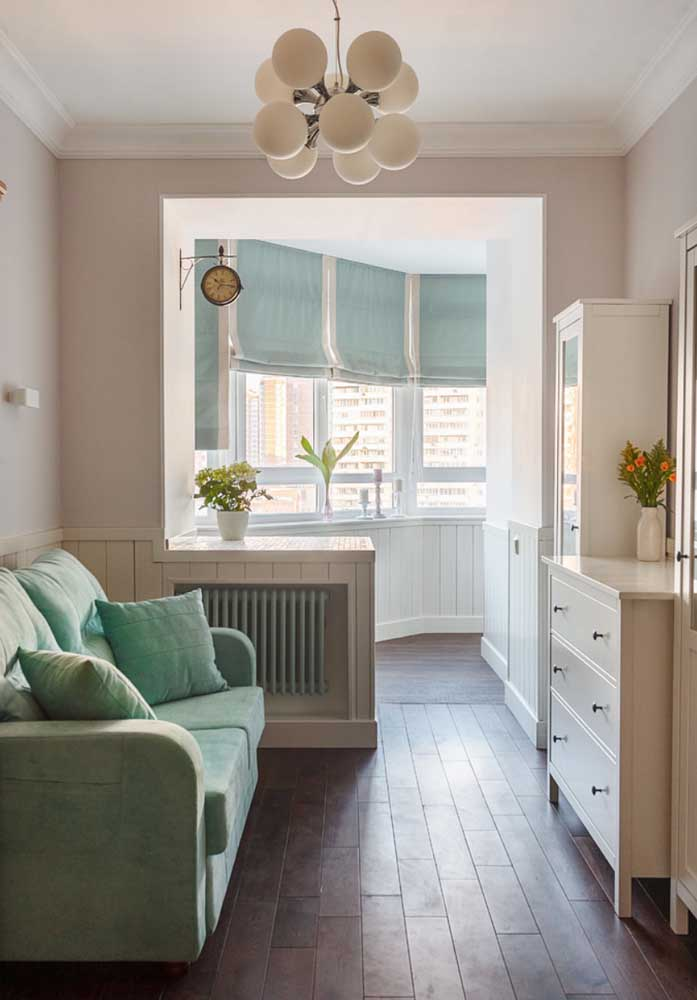 Sala de estar com toque vintage e sofá azul claro, quase na mesma tonalidade da persiana aos fundos