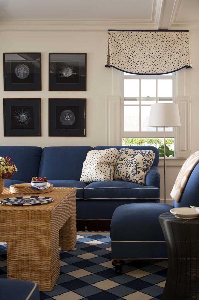 A combinação entre o azul do sofá e a mesa de vime garante um ar praiano à decoração