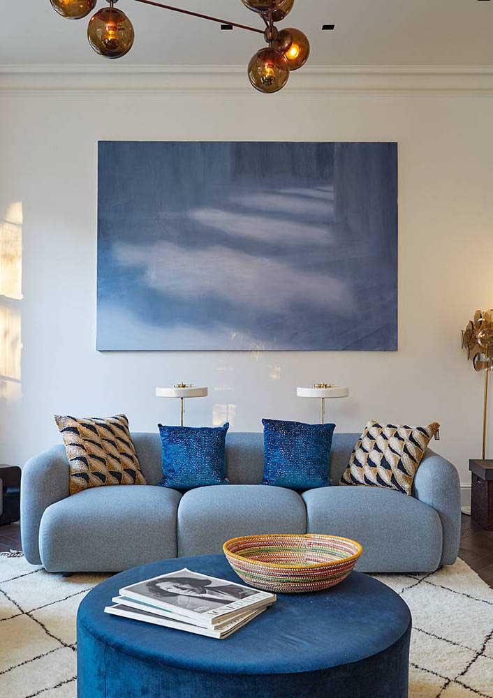 Sofá azul claro em linho e almofadas azul royal seguindo o mesmo padrão do puff e do quadro na parede