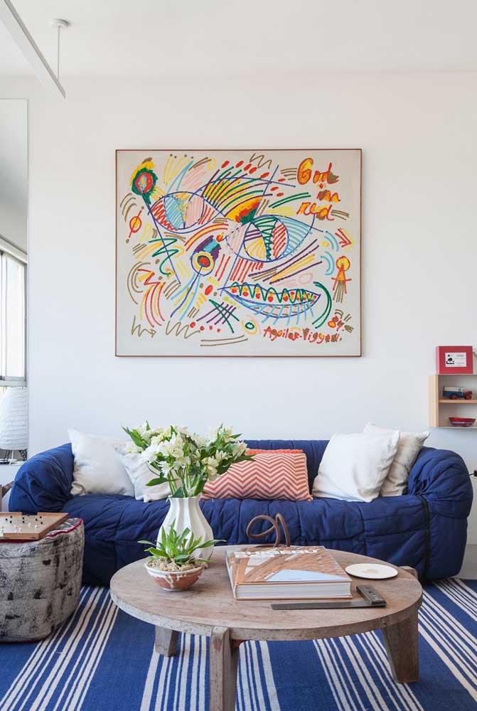 Sofá azul royal super macio e confortável preenchendo o espaço principal da sala moderna